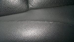 Потресканный кожзам на темном диване