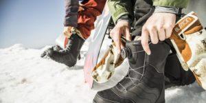 надевает ботинки для сноуборда