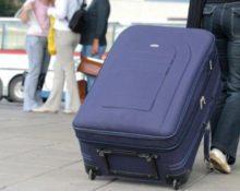 мужчина тащит чемодан