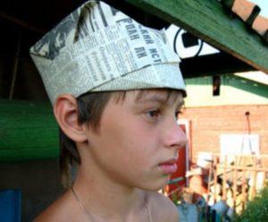 Мальчик с газетной шляпой с козырьком