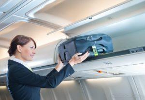 стюардесса кладет чемодан наверх