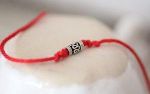 красная нитка с амулетом