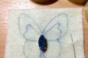 Приклеить на крылья (по центру) стразы в виде капель