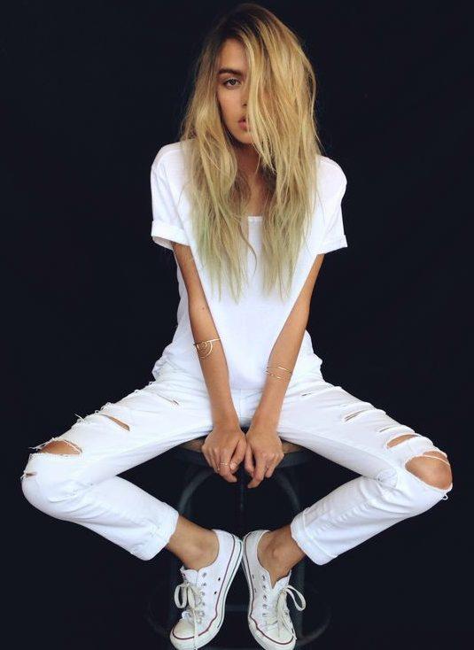 Белая футболка и рваные брюки.