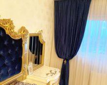 Синие шторы в спальню с кисточками.