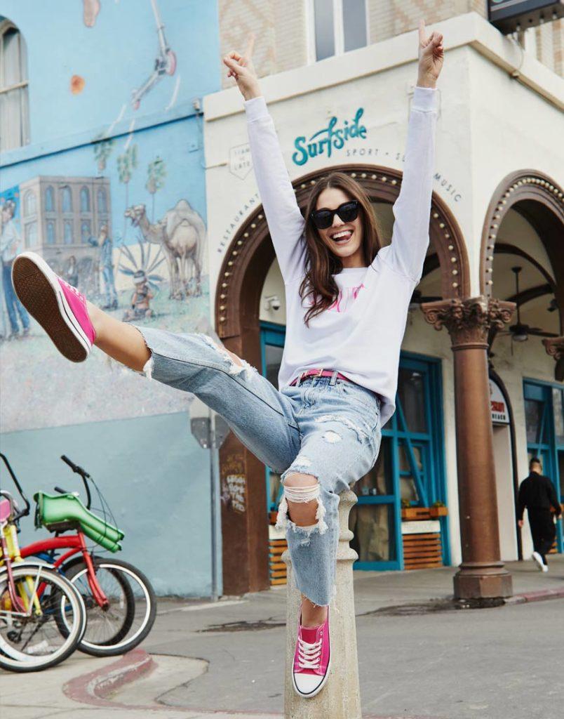 Девушка в джинсах и толстовке.