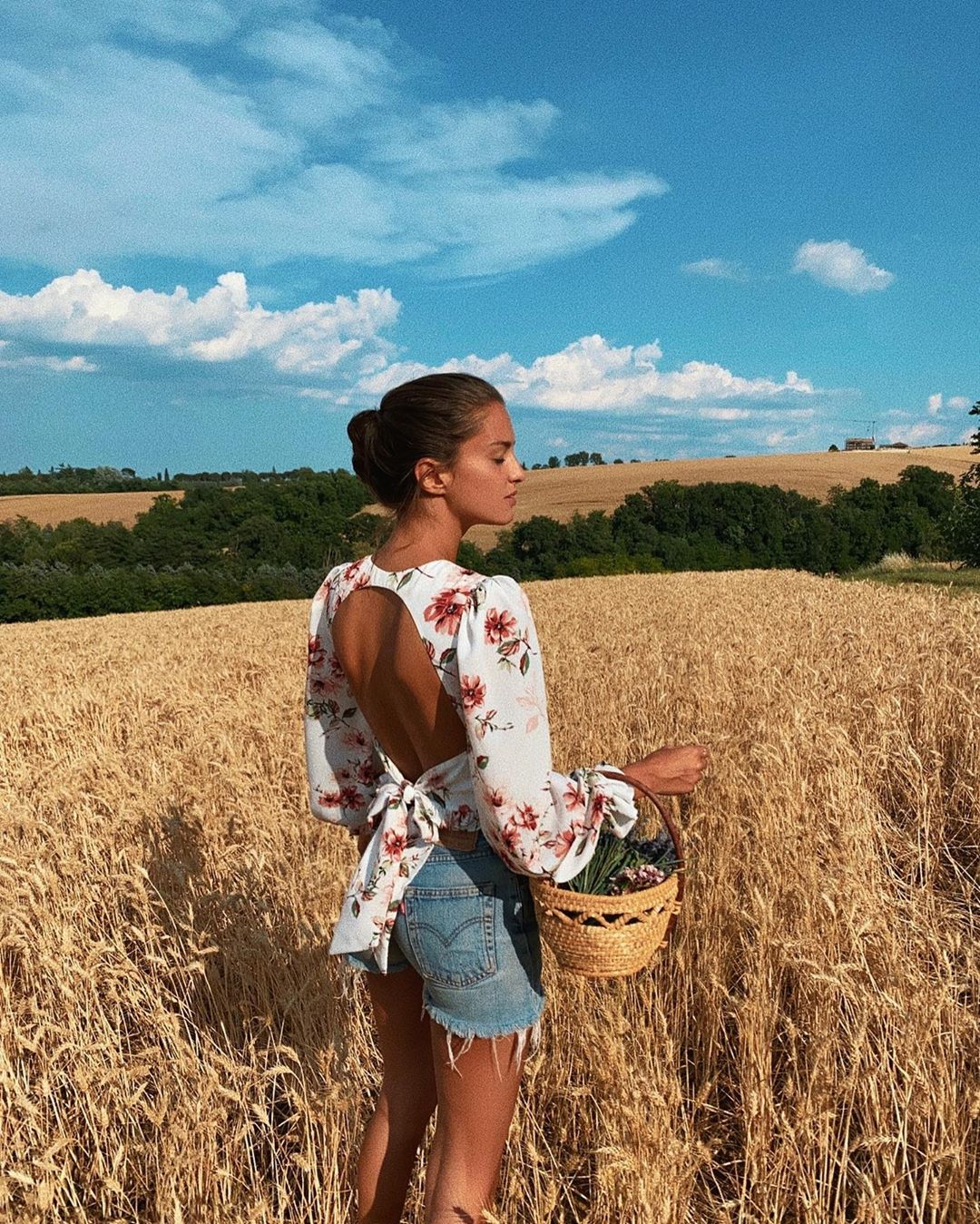 Девушка в рубашке с открытой спиной посреди поля
